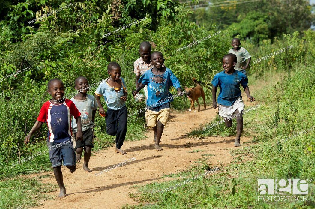 Stock Photo: Happy boys running barefoot along dirt path, Kenya, June.