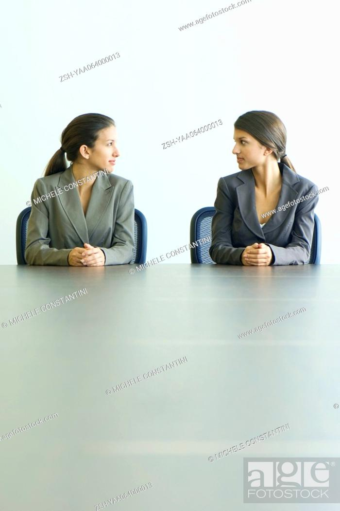 Stock Photo: Teenage twin sisters dressed in suits, sitting at table, looking at each other.