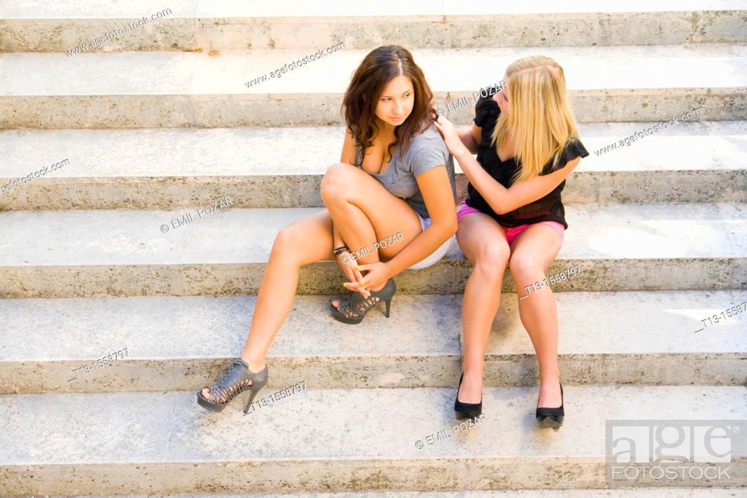 Stock Photo: Attractive young women are sitting on steps.