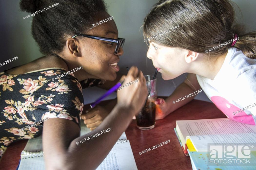 Stock Photo: African American pre Teen/ teen with glasses sipping soda in the same glass than a caucasian pre teen/teen. They are both drinking from a straw the same soda.
