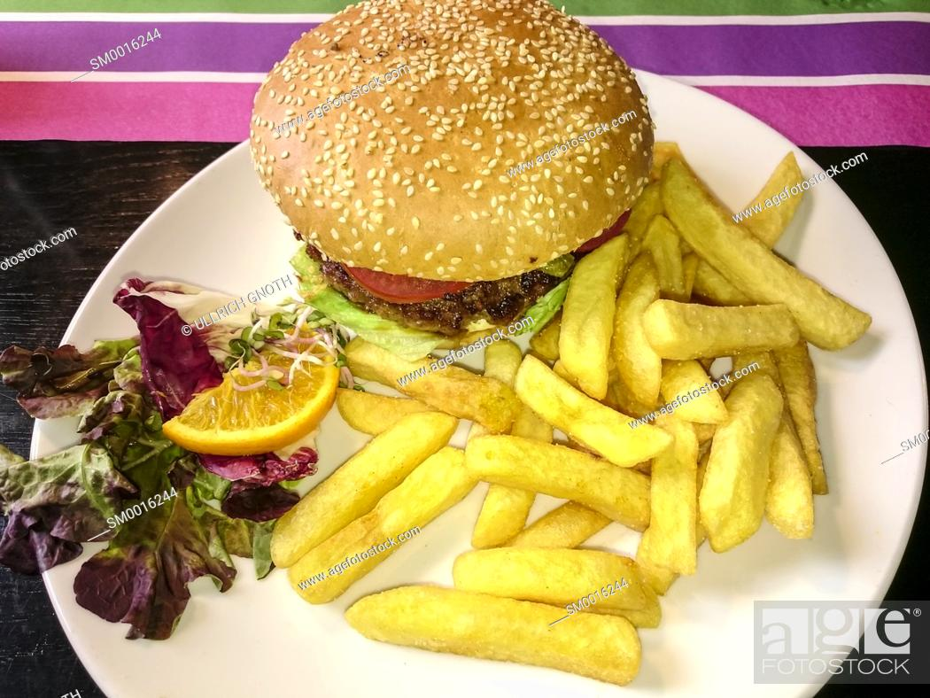 Stock Photo: Meal of freshly prepared burger, French potatoes and lettuce served on a white plate.