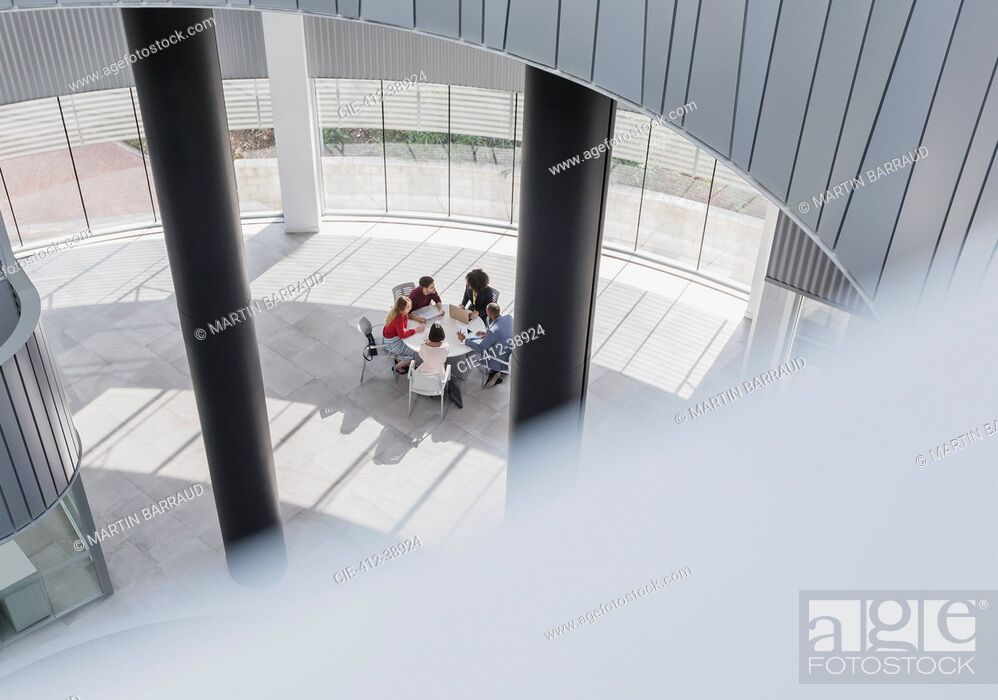 Stock Photo: Business people meeting at table in modern office atrium.