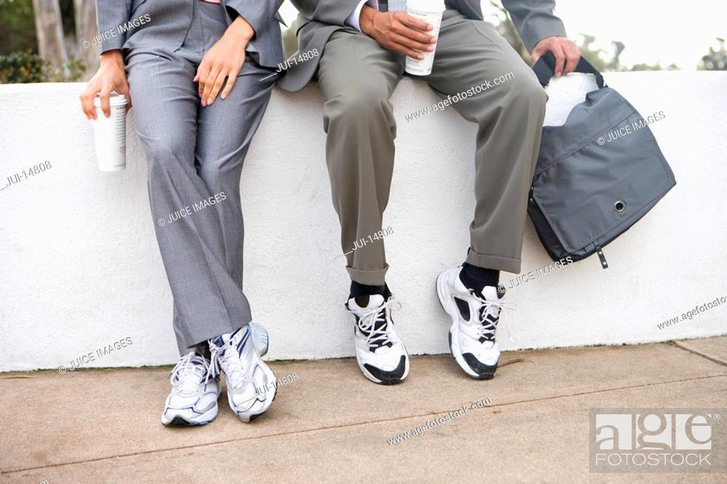 Stock Photo: Businessmen in sports shoes on wall with disposable cups, low section.