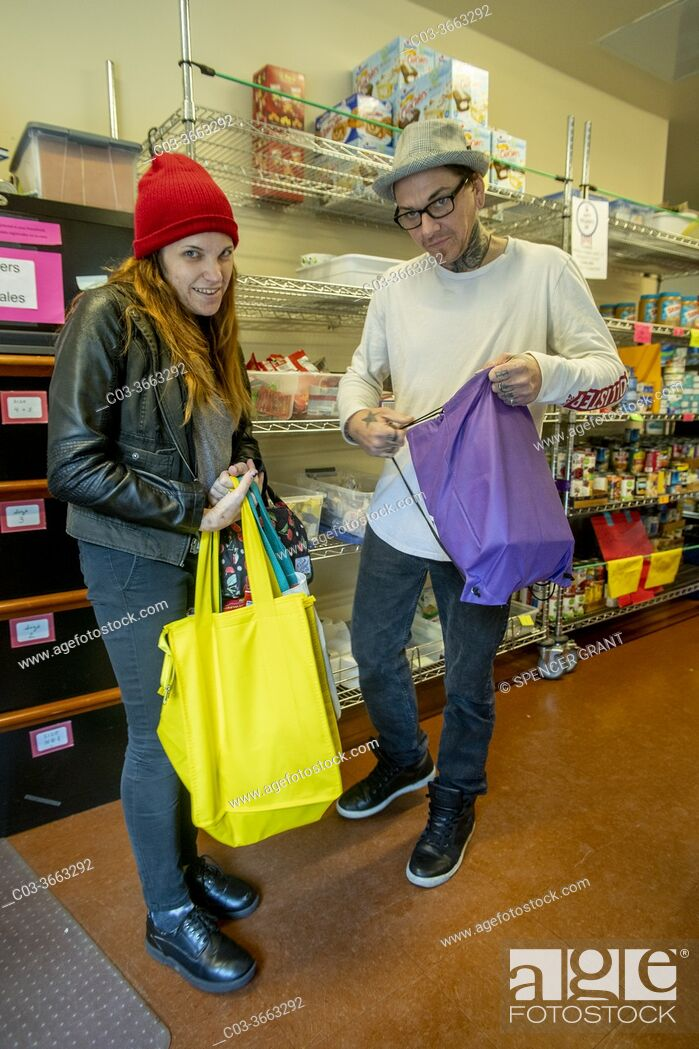 Stock Photo: Clients at the charity food pantry of a Southern California Catholic church fill their shopping bags.