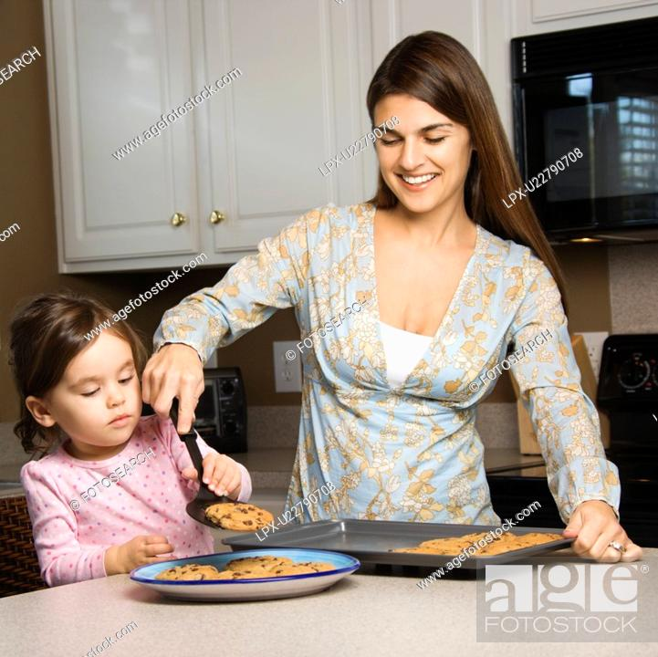 Stock Photo: Caucasian mother and daughter with cookies.