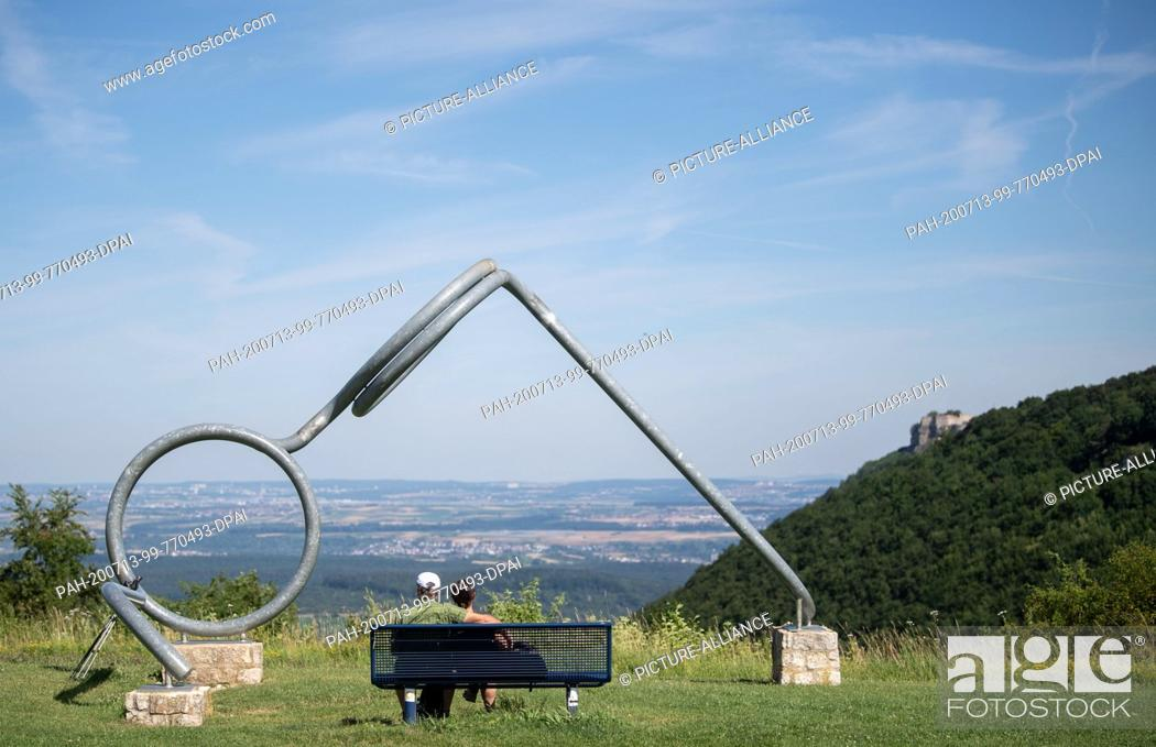 """Imagen: 13 July 2020, Baden-Wuerttemberg, Hülben: Two hikers sit on a bench at the edge of the Swabian Alb in front of the artwork """"""""Brille"""""""" by the artist Karl Schwarz."""