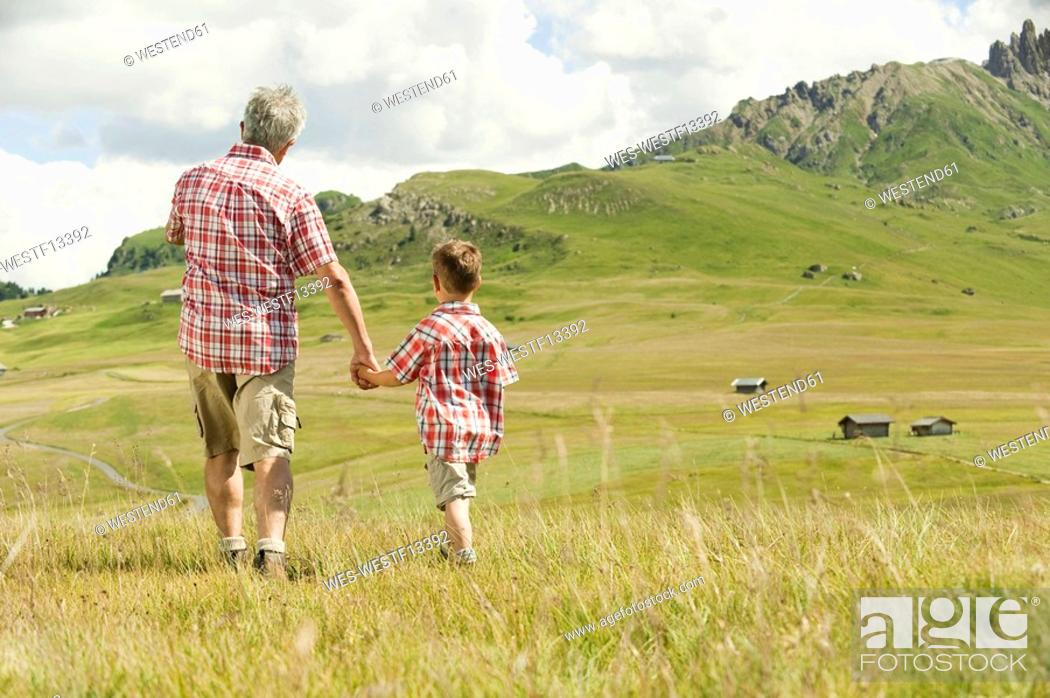 Stock Photo: Italy, Seiseralm, Grandfather and grandson 6-7 walking in field, rear view.