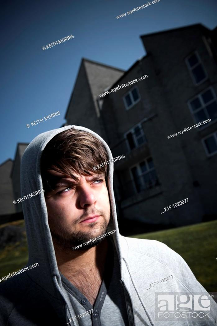 Stock Photo: Young man wearing hoodie standing outside a block of flats.