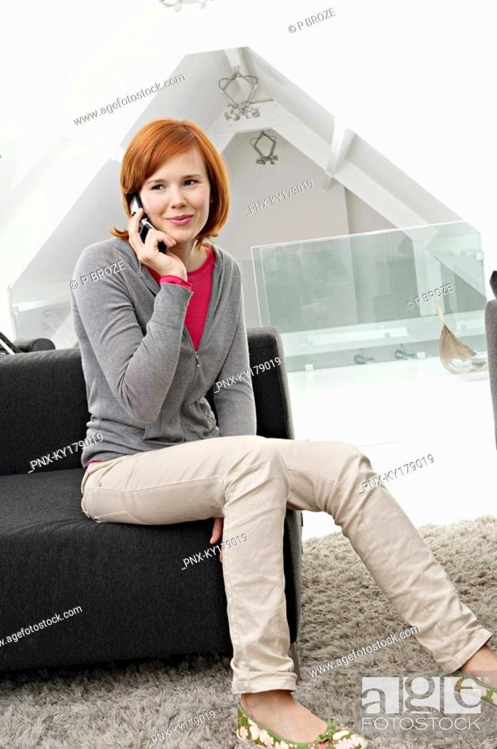 Stock Photo: Young woman sitting on a couch and using a mobile phone.