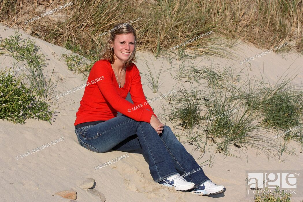 Stock Photo: Young blonde woman outdoors. Sitting on sand dune at the beach.