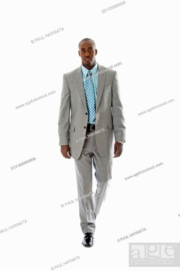 Stock Photo: Handsome African American man in gray suit walking, isolated.