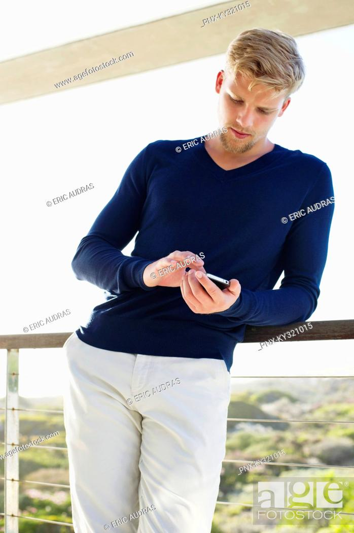 Stock Photo: Young man using a mobile phone at a balcony.