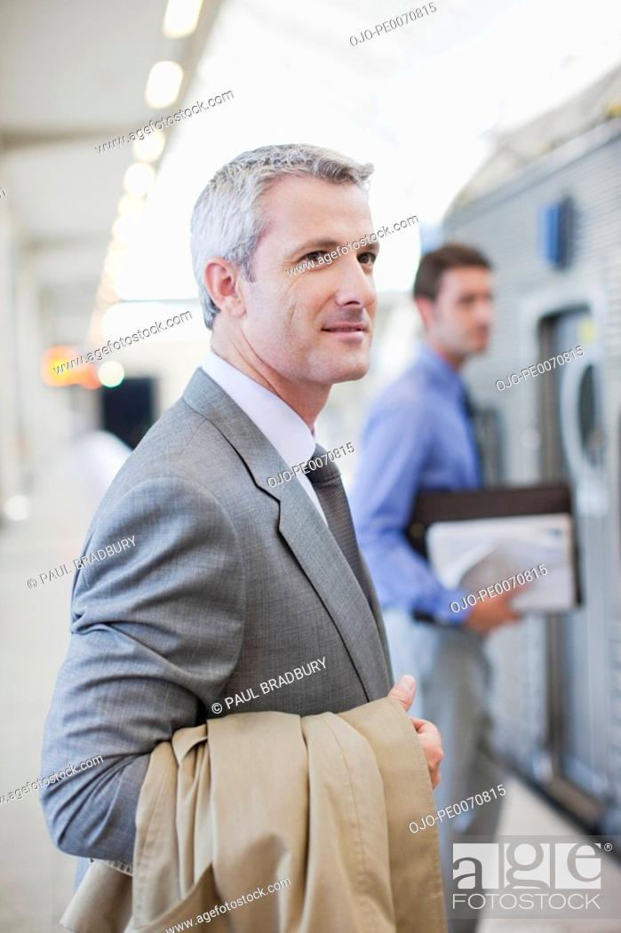Stock Photo: Businessman waiting for train in train station.
