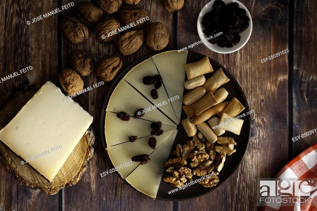 Stock Photo: Slices and piece of traditional Spanish Manchego cheese, raisins and nuts on dish on wood table and blue background from above.