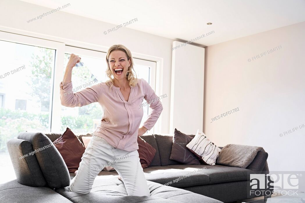 Stock Photo: Portrait of exuberant woman posing on couch at home.