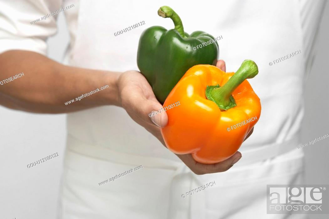 Stock Photo: Chef holding two bell peppers (mid section).