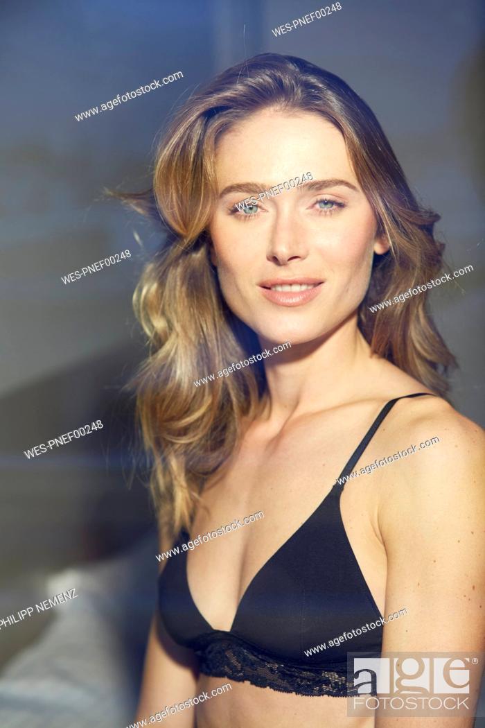 Stock Photo: Portrait of woman wearing black bra behind windowpane.