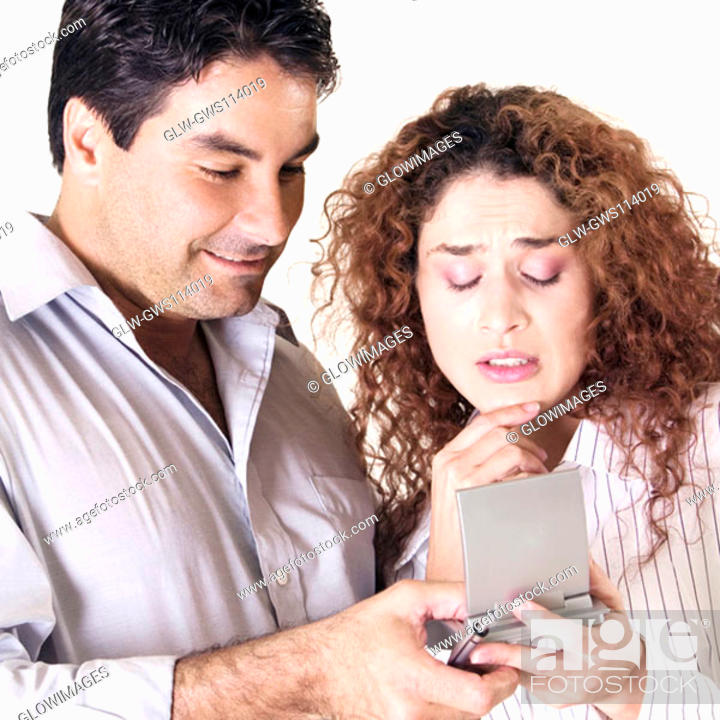 Stock Photo: Close-up of a young woman and a mid adult man using a calculator.