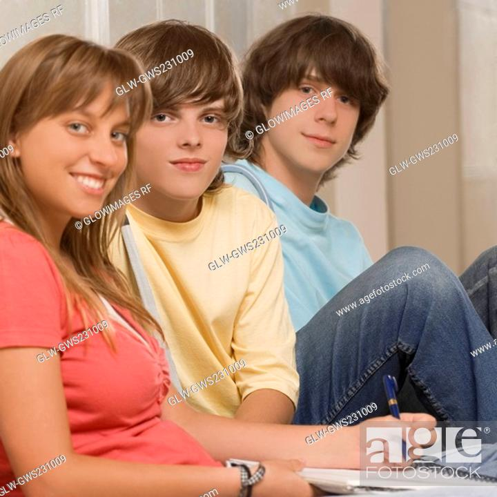 Stock Photo: Portrait of a teenage girl smiling with her friends sitting beside her.