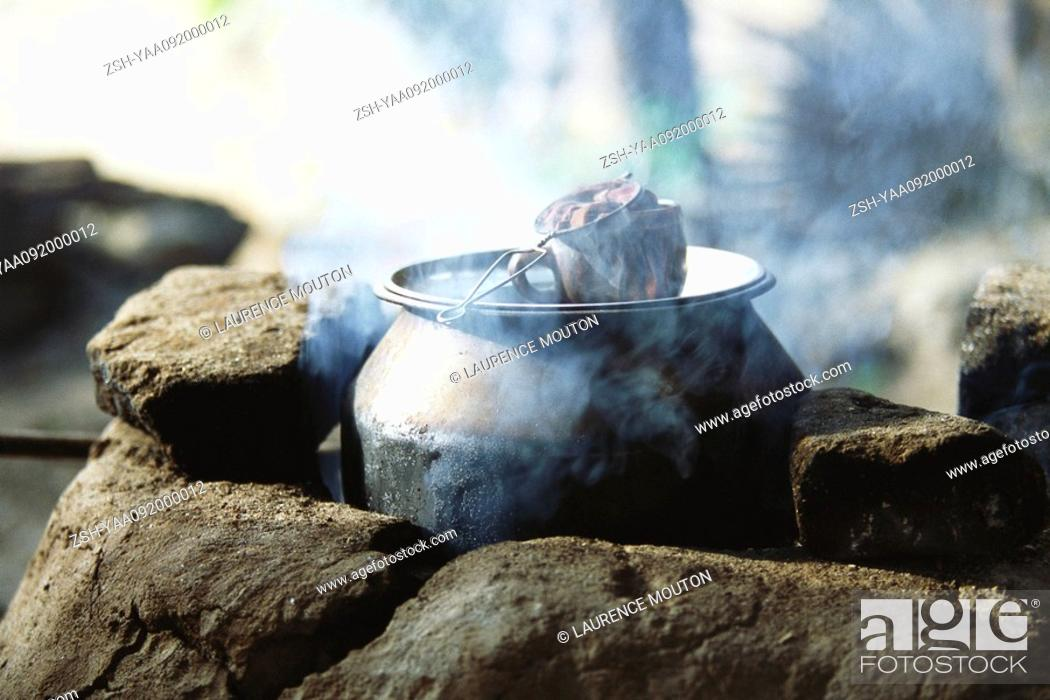 Stock Photo: Tea steeping in cup placed atop cast iron pot cooking on traditional stove.