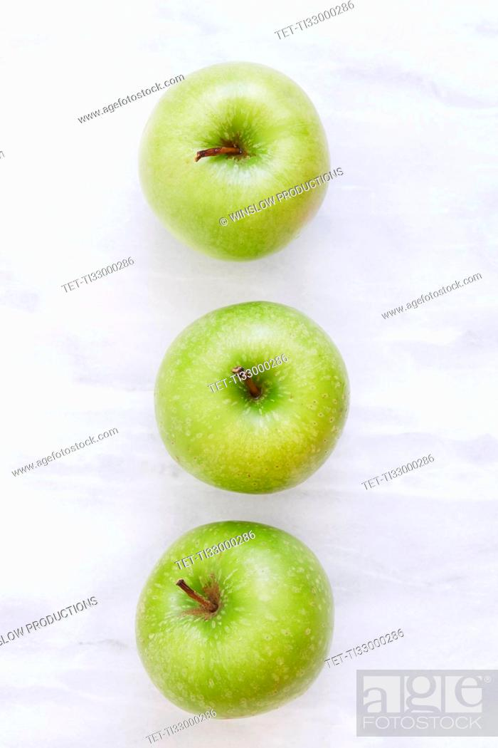Stock Photo: Overhead view of three apples on marble table.
