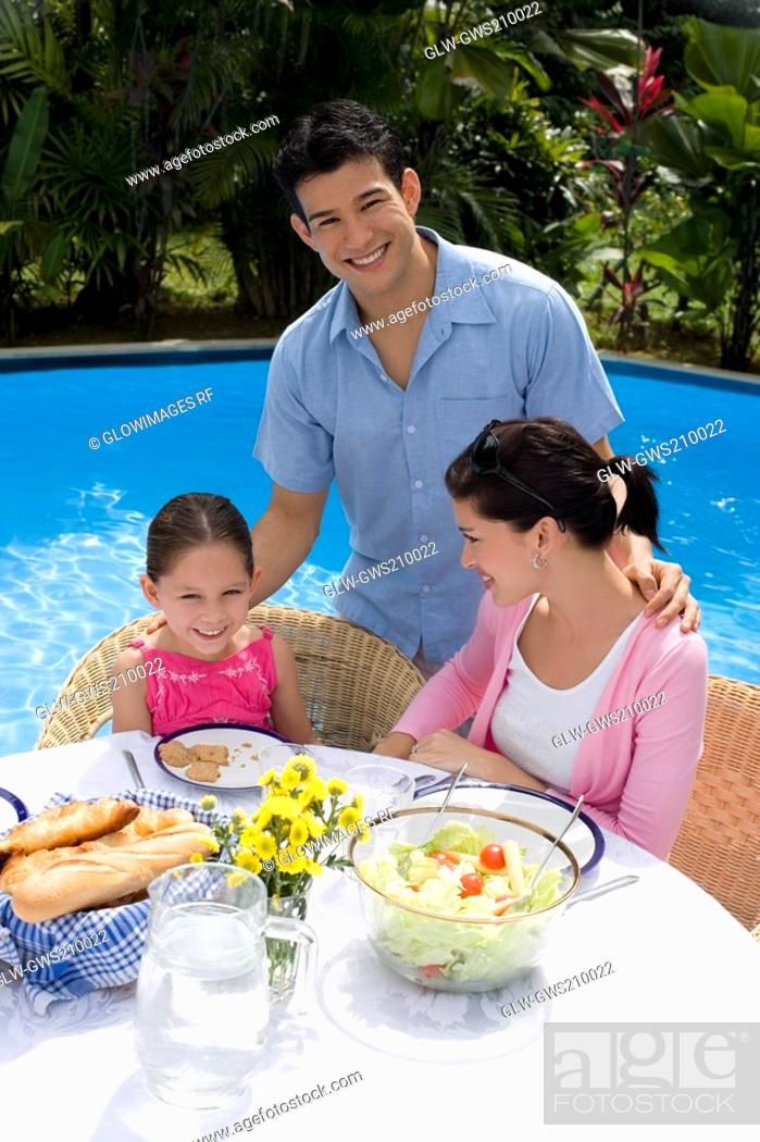 Stock Photo: Young couple with their daughter at a breakfast table and smiling.