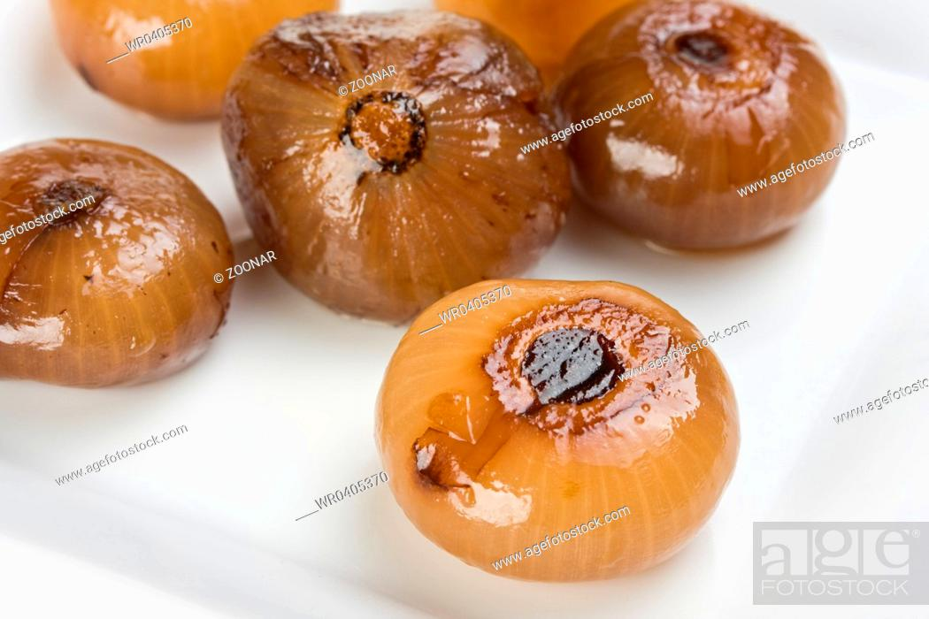 Stock Photo: pickeled onions on a white plate.