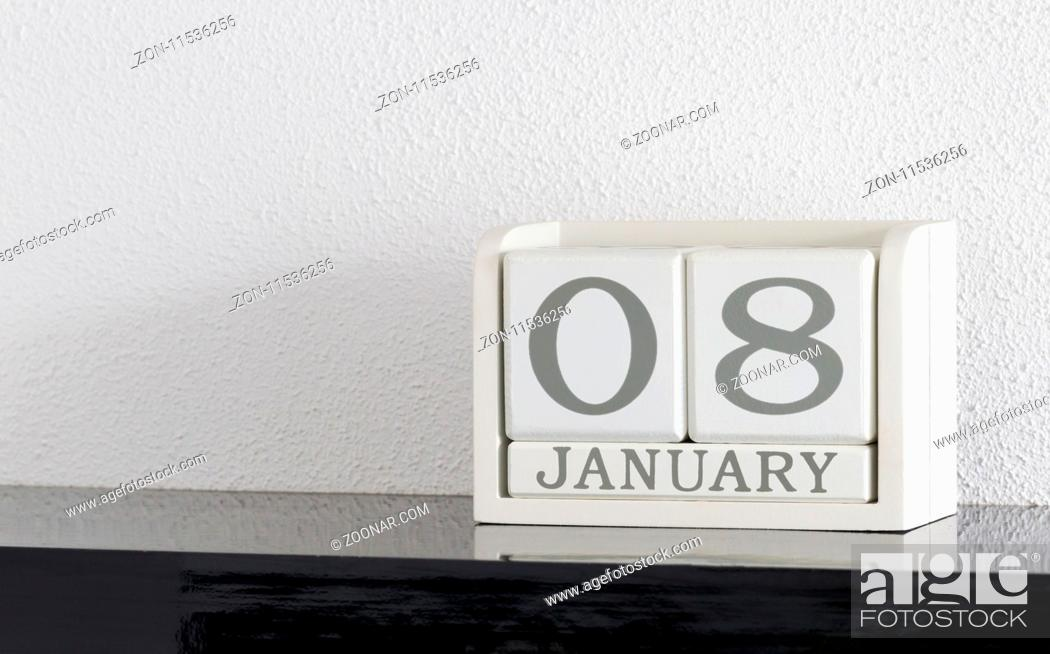 Imagen: White block calendar present date 8 and month January on white wall background.