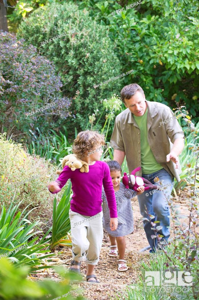 Stock Photo: Father with two children walking in a garden.