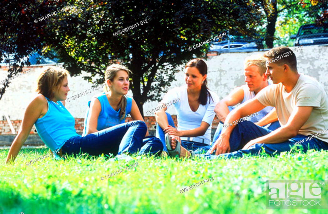 Stock Photo: A group of young people sitting on a lawn.