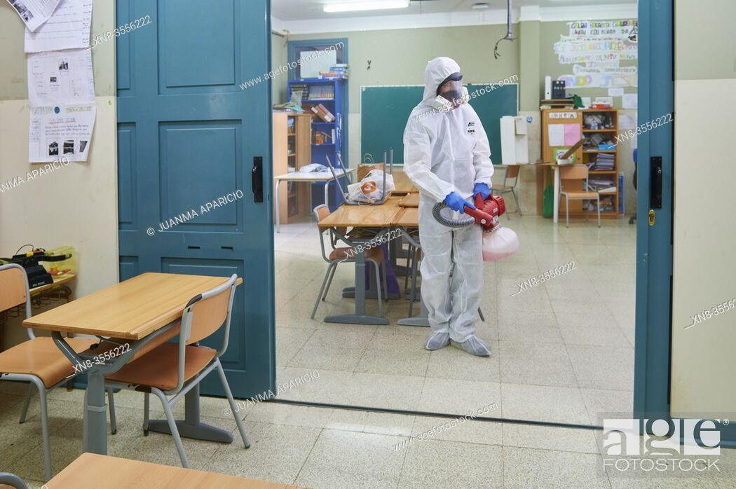 Stock Photo: Worker in protective suit disinfect interior of the school.