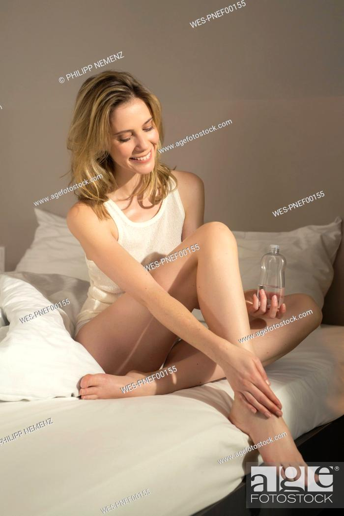Stock Photo: Smiling woman in bed applying skin oil.