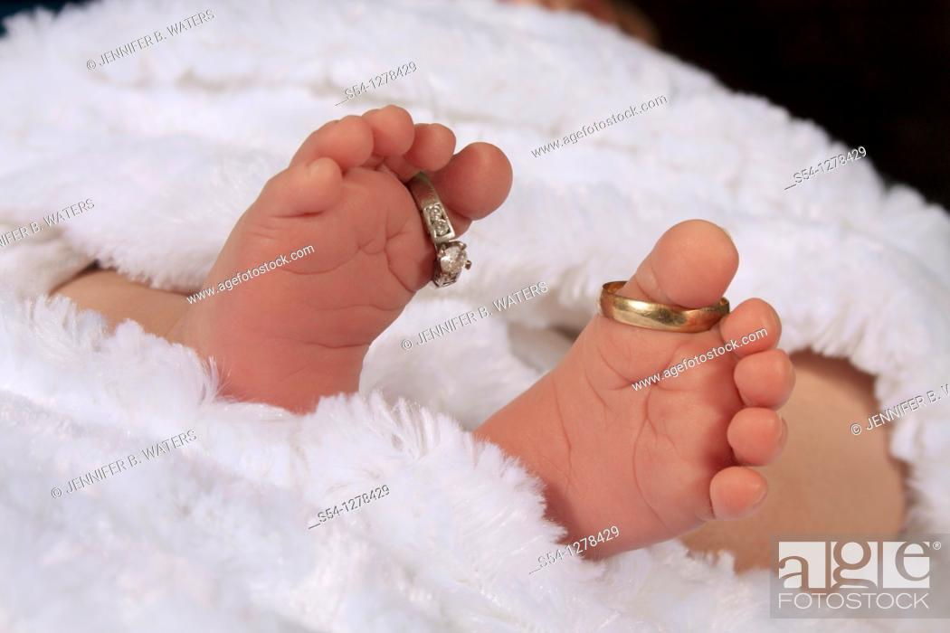 Stock Photo: A newborn baby's feet, with the parents' wedding rings on his toes.