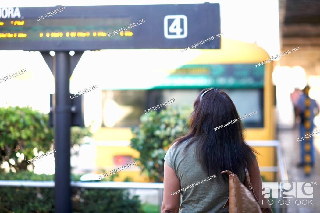 Stock Photo: Rear view of woman strolling to railway platform.