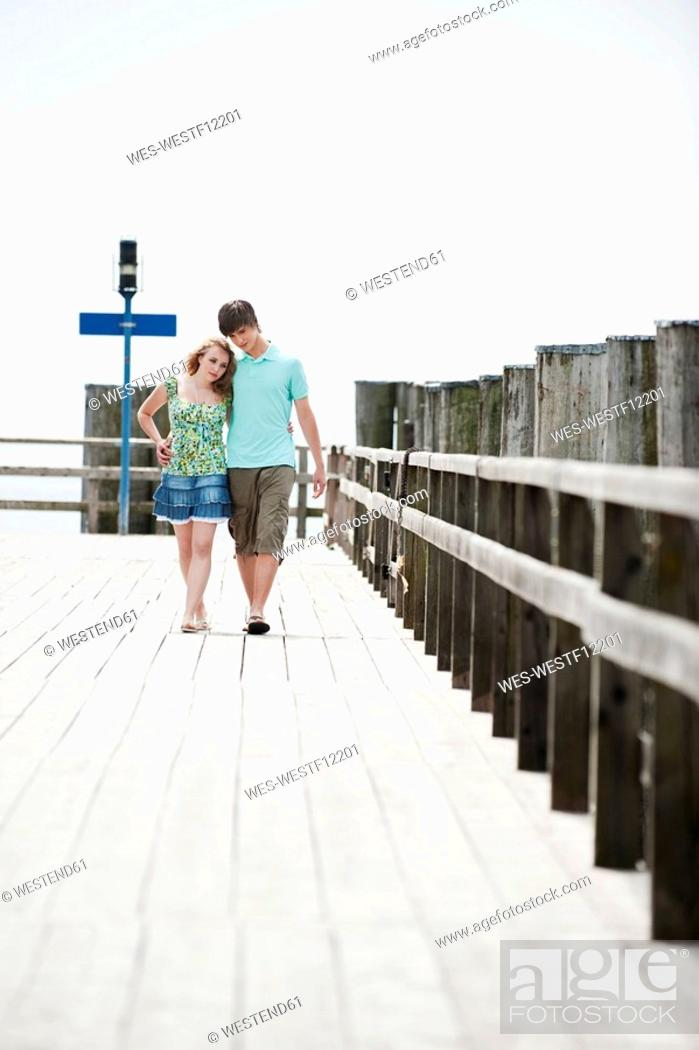 Stock Photo: Germany, Bavaria, Ammersee, Couple walking across pier.