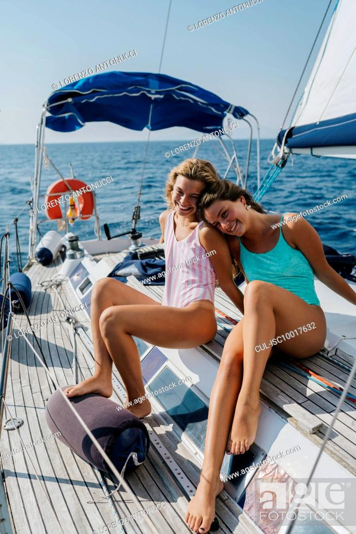 Imagen: Friends relaxing on deck of sailboat, Italy.