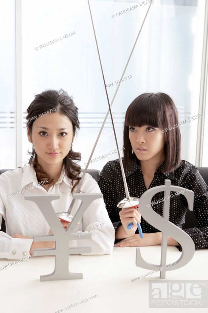 Imagen: Young women with holding sword and with yen sign and dollar sign in foreground.