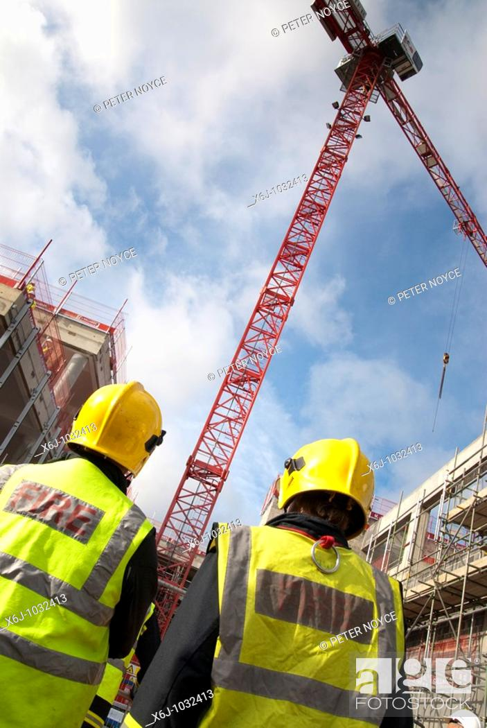 Stock Photo: rear view of two fire officers on construction site with tower crane.