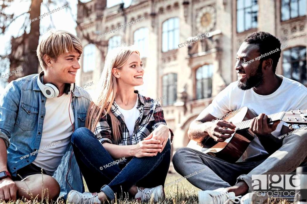 Stock Photo: Creative person. Handsome positive afro American man looking at his friends and smiling while playing the guitar.