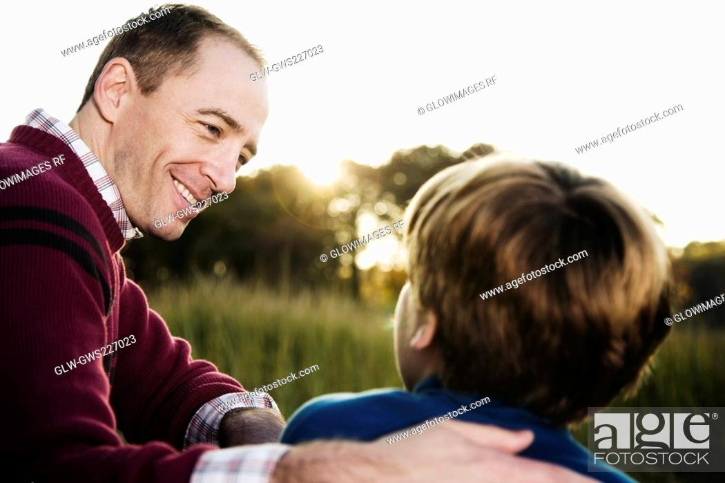 Stock Photo: Mid adult man sitting with his son and smiling.
