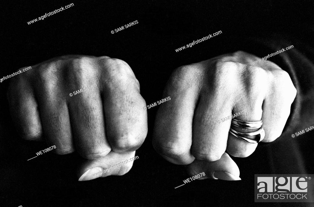 Stock Photo: Woman clenching two hands into fists in a fit of aggression.