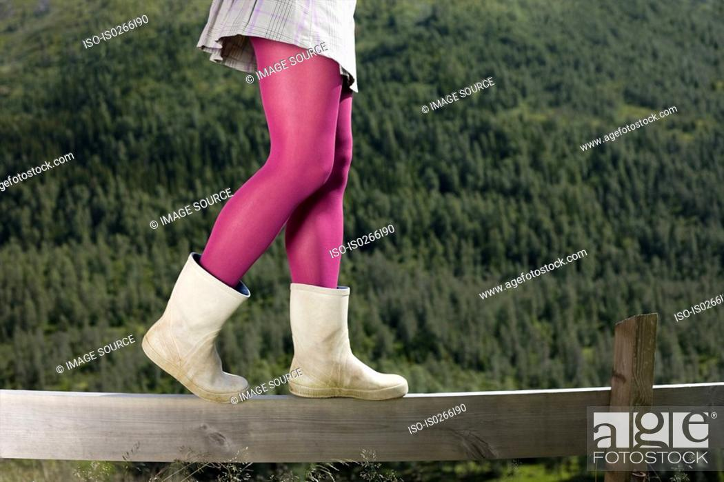 Stock Photo: Girl walking on a wooden fence.