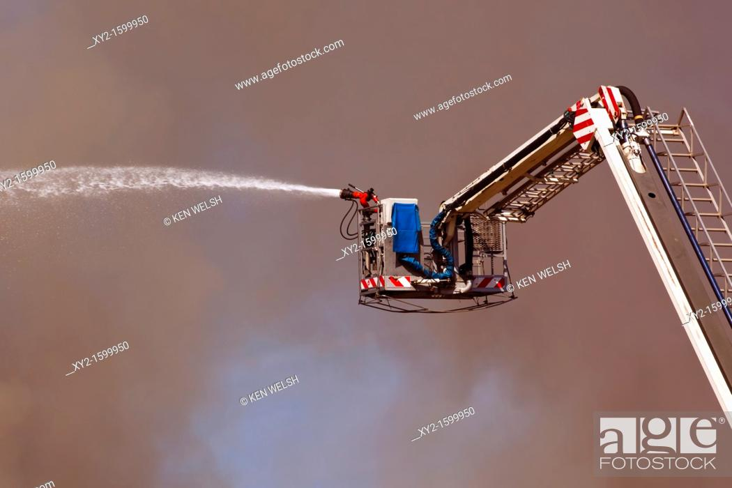 Stock Photo: Torremolinos, Malaga Province, Costa del Sol, Spain  Fighting fire which burned down The Magic Palace, February 18, 2011 with remote controlled hose on ladder.