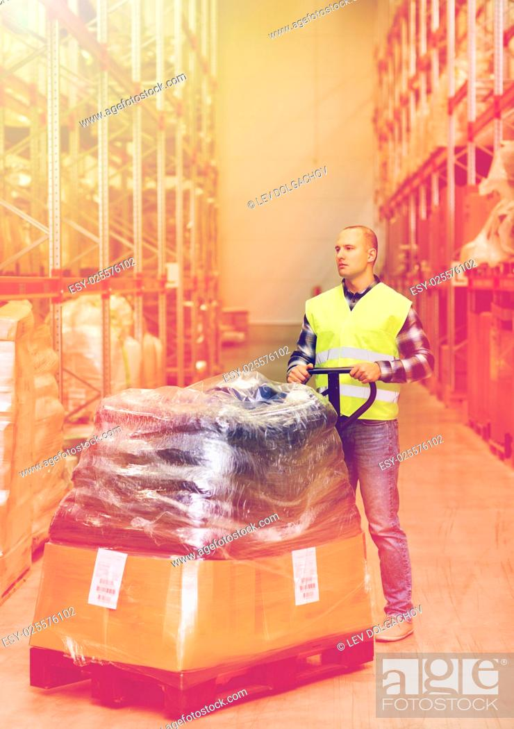 Stock Photo: wholesale, logistic, loading, shipment and people concept - man carrying loader with goods at warehouse.