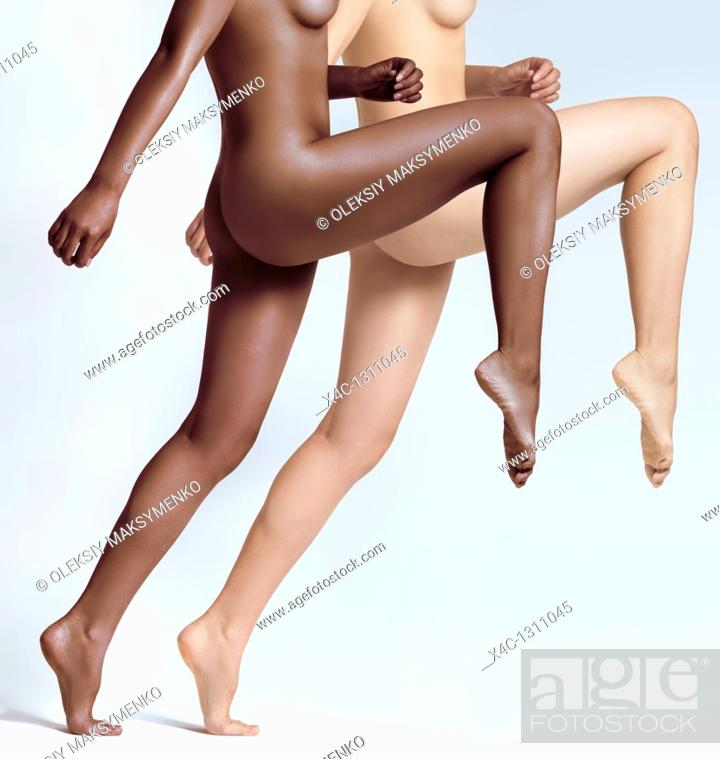 Stock Photo: Dynamic photo of two young naked woman with black and white skin gracefully leaping forward.