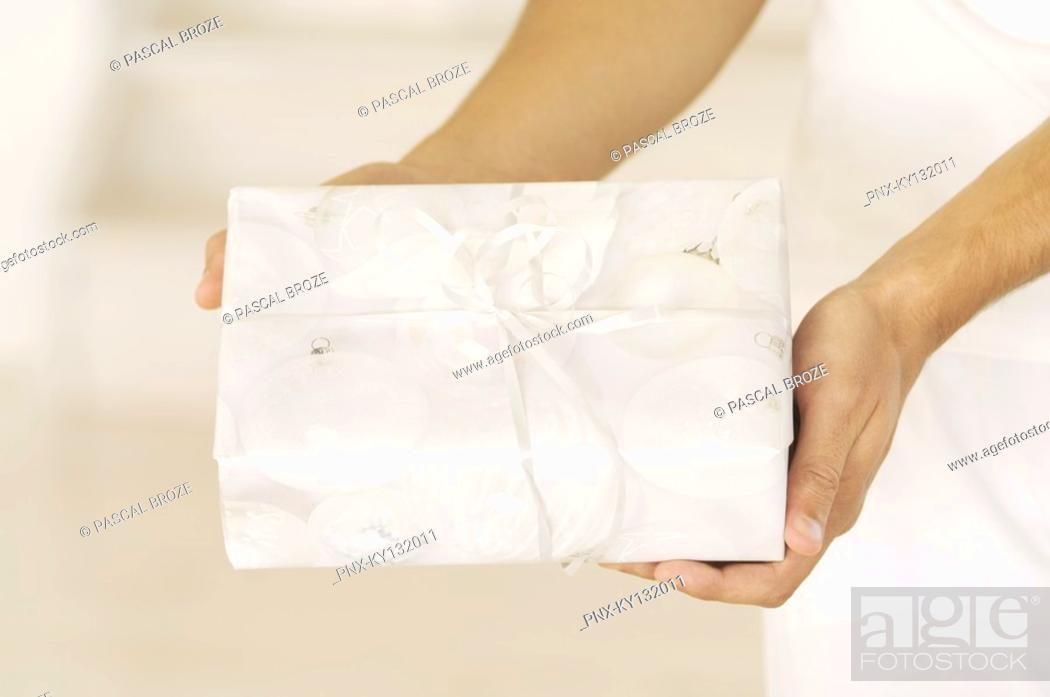 Stock Photo: Man hand holding a present, close-up, indoors.