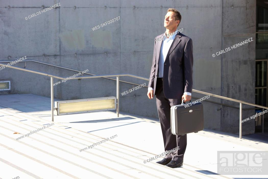 Stock Photo: Germany, Bavaria, Munich, Businessman standing on stairs with briefcase.