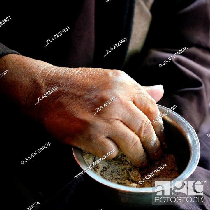 Stock Photo: India, Jammu and Kashmir State, Himalaya, Ladakh, hand of a man eating Tsampa, barley flour mixed with salty butter tea in a bowl.
