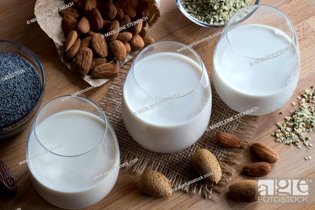 Stock Photo: Three glasses of vegan plant milk - almond milk, poppy seed milk and hemp seed milk, with shelled and unshelled almonds, poppy seeds and hemp seeds on a wooden.