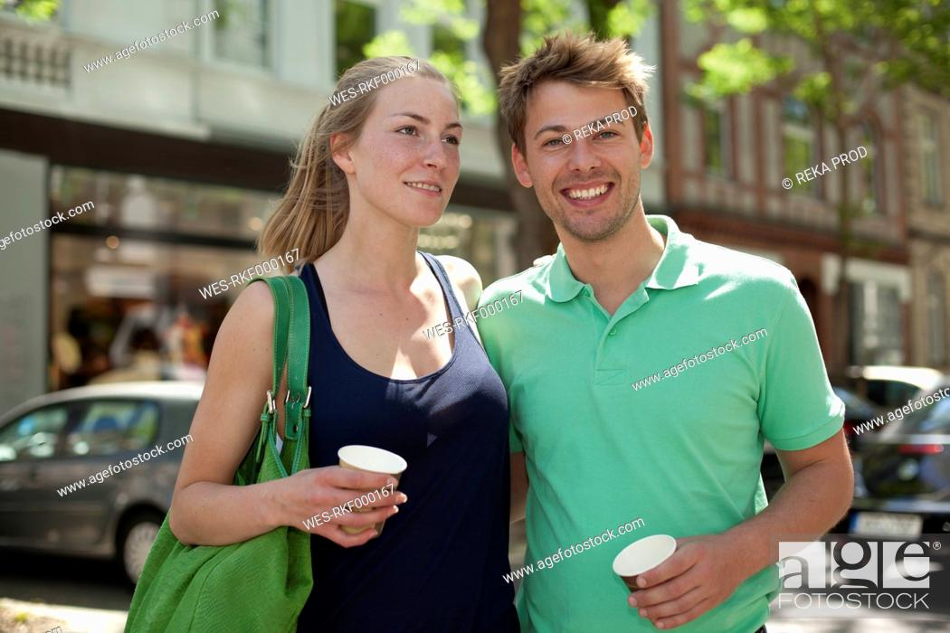 Stock Photo: Germany, North Rhine Westphalia, Duesseldorf, Couple with coffee cup, smiling.